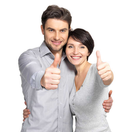 Portrait of happy couple with thumbs up sign isolated on white background Фото со стока