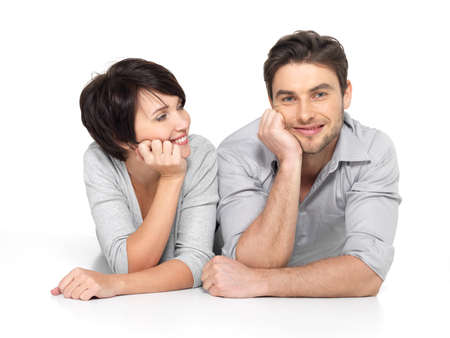man lying down: Portrait of happy couple isolated on white background. Attractive man and woman being playful.