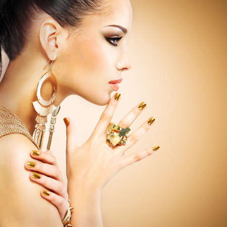 nail art: Profile portrait of the beautiful fashion woman with black makeup and golden manicure