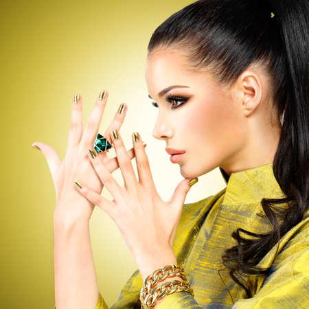 perfil de mujer rostro: Glamour mujer con las uñas hermosas de oro y el anillo de esmeralda en las manos
