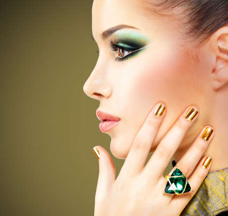 nail studio:  Glamour woman with beautiful golden nails and emerald ring on hands
