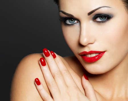 lips red: Foto de la mujer con las uñas rojas de la moda y los labios sensuales - Modelo posando en el estudio