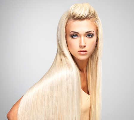 cabello rubio: Mujer hermosa con largos pelos rubios rectas. Moda modelo posando en el estudio.