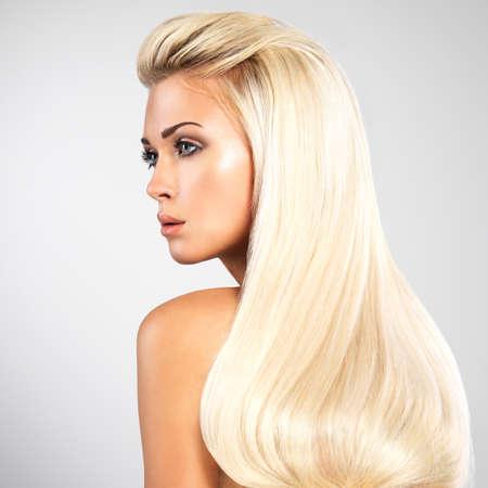 cabello lacio: Mujer hermosa con largos pelos rubios rectas. Moda modelo posando en el estudio.
