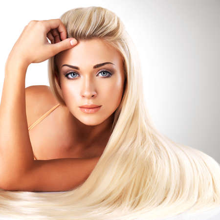 long blonde hair: Beautiful woman with long straight blond hair. Fashion model posing at studio.