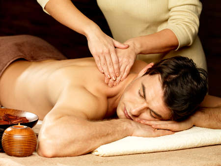 male massage: Masseur massaging man in the spa salon. Beauty treatment concept.