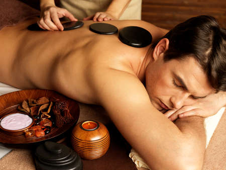 spa therapy: Handsome man having stone massage in spa salon. Healthy lifestyle.
