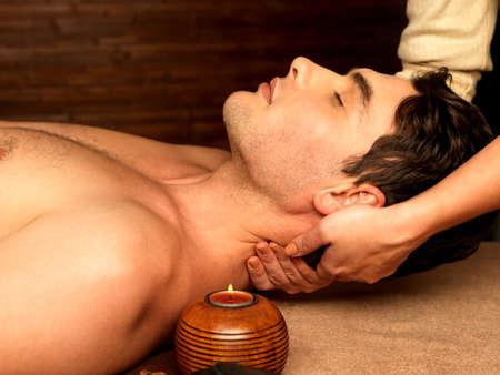 massaggio: Massaggiatore facendo massaggio al collo sull'uomo nel salone spa.
