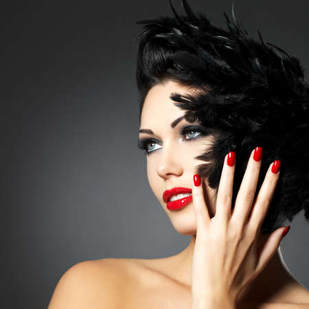 nails woman: Beautiful fashion woman with red nails, creative hairstyle and makeup - Model posing in studio