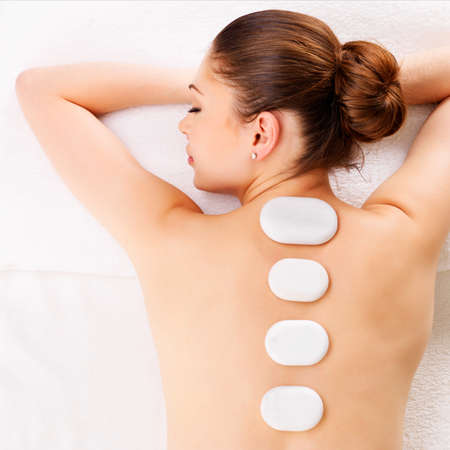 Adult woman relaxing in spa salon having therapy with hot\ stones on backbone