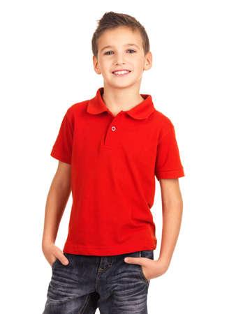 sorrisos: Menino bonito novo que levanta no estúdio como um modelo de moda. Foto de pré-escolar 8 anos de idade sobre o fundo branco