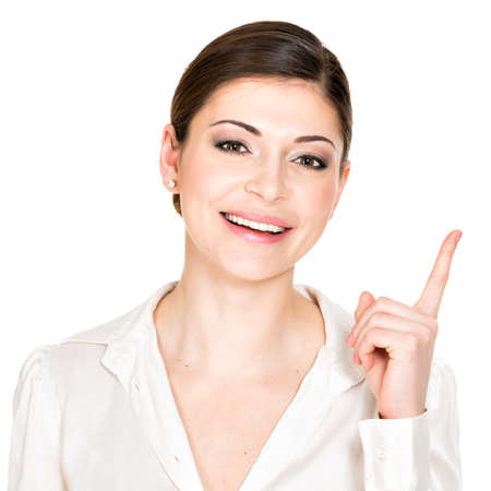 Closeup portrait of the young happy woman with points up sign  in white shirt -  isolated on white background. photo
