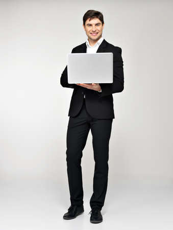 Full portrait of smiling happy businessman with laptop  in black suit at studio. Concept communication.  photo