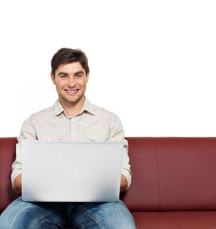 Portrait of smiling happy man with laptop sits on the divan, isolated on white.   Stock Photo