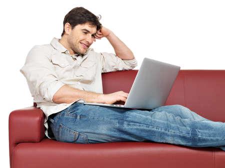 divan: Retrato de hombre sonriente feliz con la computadora port?til se sienta en el div?n, aislado en blanco.
