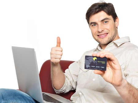 Portrait of smiling happy man with laptop gives the thumbs up and shows the credit card isolated on white. 