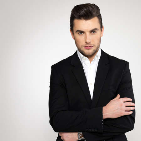 conceited: Fashion young businessman black suit casual  poses at studio