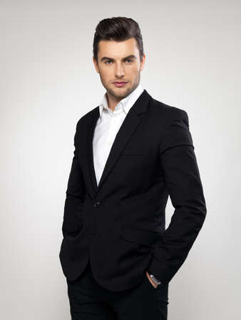 male model: Fashion young businessman black suit casual  poses at studio