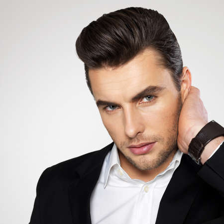 Closeup Gesicht eines fashion junge Geschäftsmann im schwarzen Anzug lässig posiert im Studio