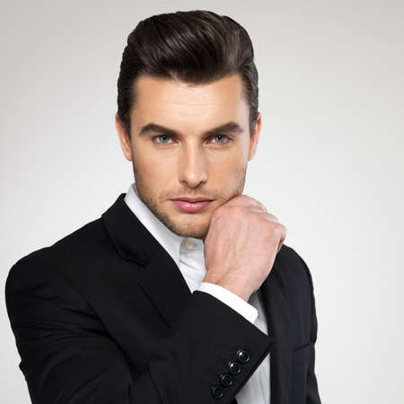 male hair model: Fashion young businessman black suit casual  poses at studio