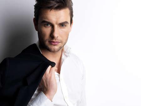modelos hombres: Hombre Moda joven en camisa blanca tiene la chaqueta negro sobre pared con las sombras de contraste
