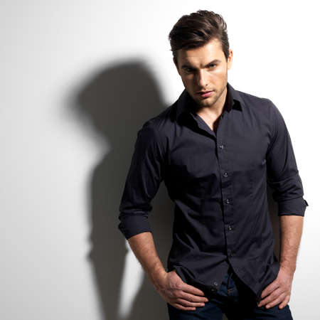 man in shadow: Fashion portrait of young man in black shirt poses over wall with contrast shadows
