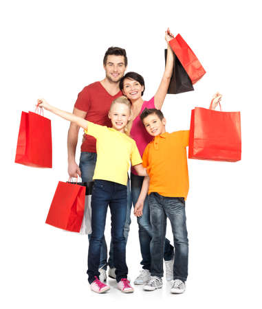 shopping bags: Happy family with shopping bags standing at studio over white background