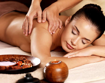 massaging: Masseur doing massage on woman body in the spa salon. Beauty treatment concept.