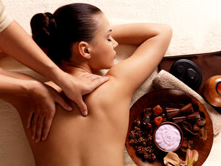 vertical: Masseur doing massage on woman body in the spa salon. Beauty treatment concept.