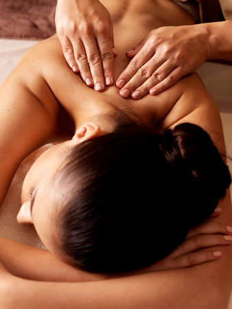 spa candle: Masseur doing massage on woman body in the spa salon. Beauty treatment concept.