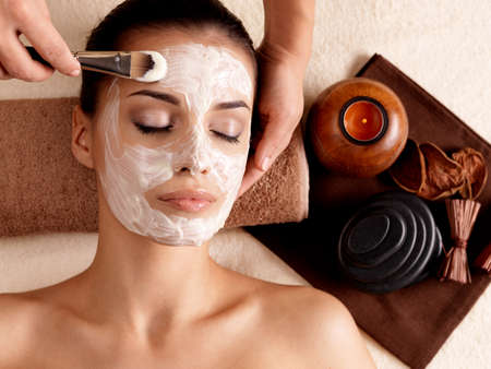 beauty spa: Spa therapy for young woman receiving facial mask at beauty salon - indoors