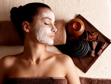 female mask: Young woman relaxing with facial mask on face at beauty salon- indoors LANG_EVOIMAGES
