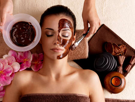 chocolate mask: Spa therapy for young woman receving cosmetic mask at beauty salon - indoors
