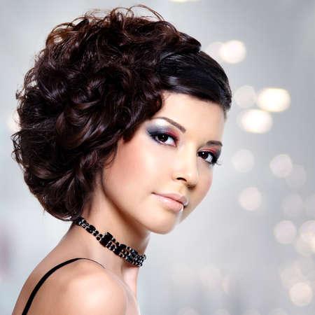 cabello casta�o claro: Joven y bella mujer con peinado rizado y maquillaje brillante