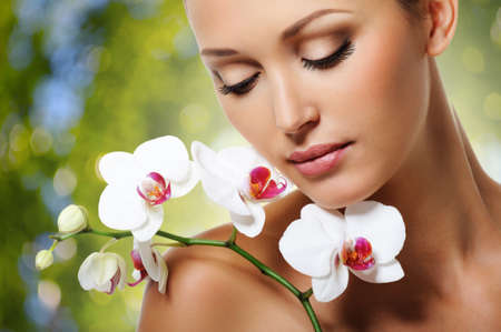 beautiful face: Beauty face of  beautiful woman with a white orchid flower. Skin care treatment. Green nature background