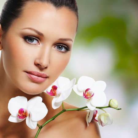 clear skin: Beauty face of  beautiful woman with a white orchid flower. Skin care treatment.