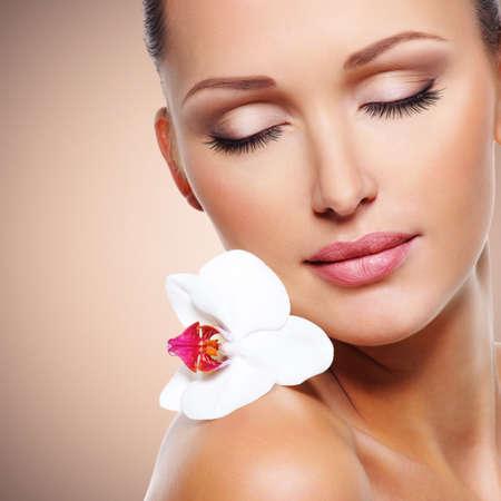 piel rostro: Cara de la belleza de la mujer hermosa con una flor de orqu�dea blanca. Tratamiento de cuidado de la piel.