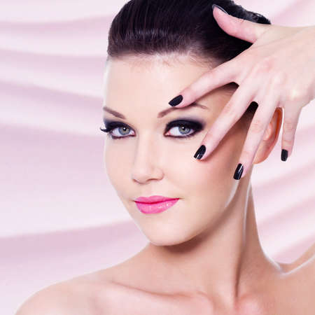 Portrait of the beautiful woman with black nails and makeup photo