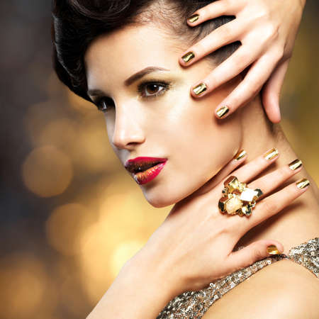 minx: Beautiful fashion woman with golden nails and gold ring over style background