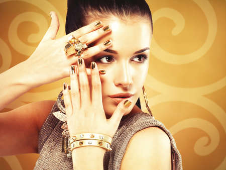 minx: Beautiful woman with golden nails and beautiful gold ring over creative background LANG_EVOIMAGES