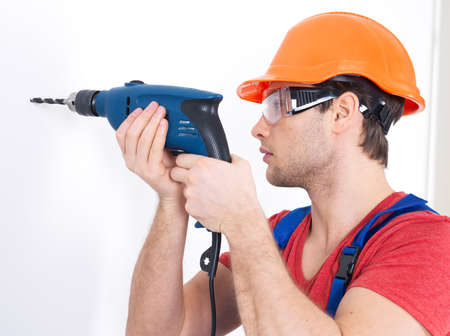 Portrait of a man drilling a hole in the wall. photo