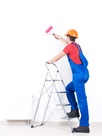 Craftsman painter stands on the stairs with roller, full portrait over white background , rear view Stock Photo - 22587379