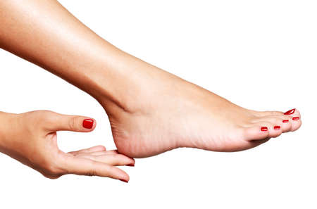 manicure: Closeup photo of a female feet with beautiful red pedicure over white background
