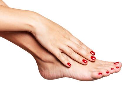 白い背景の上の美しい赤いペディキュアと女性の足のクローズ アップ写真 写真素材