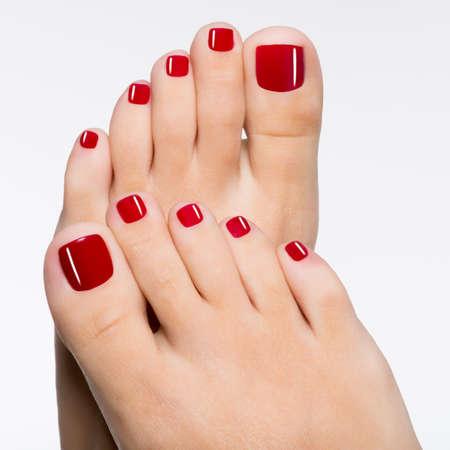 白で隔離される赤いペディキュア美しい女性の足のクローズ アップ写真