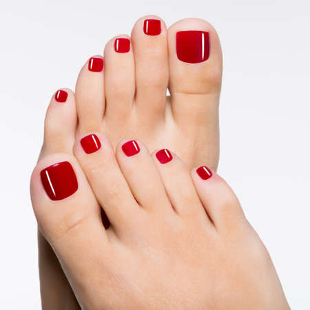 pedicura: Foto de detalle de una hermosa pies femeninos con pedicure rojo aislado en blanco LANG_EVOIMAGES