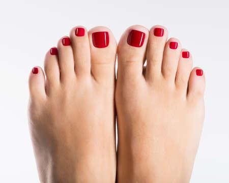Close-up foto van een mooie vrouwelijke voeten met rode pedicure op wit wordt geïsoleerd Stockfoto
