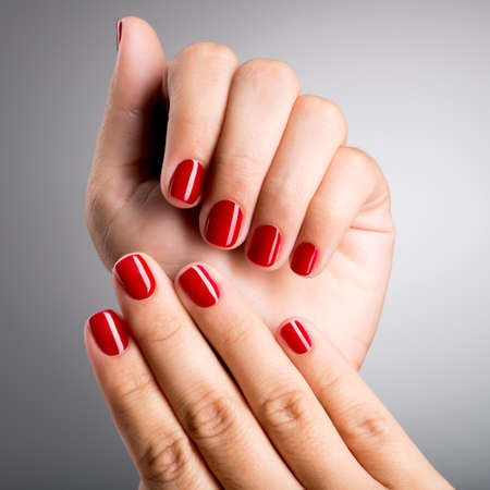 nails: Closeup photo of a beautiful female hands with red nails LANG_EVOIMAGES
