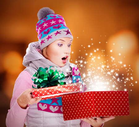 cadeau anniversaire: Photo de la femme surprise regarde dans la bo�te de No�l avec des lumi�res brillantes magie de ce - sur les lumi�res de la nuit