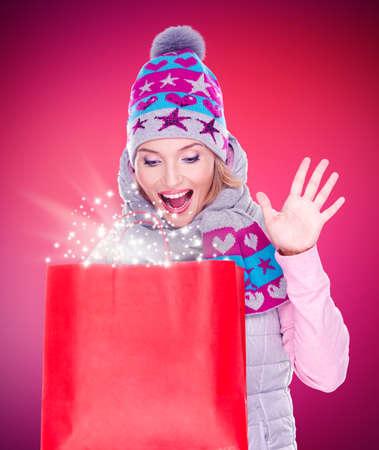 Photo de la femme heureuse surprise avec des cadeaux après le shopping à la nouvelle année à la boutique